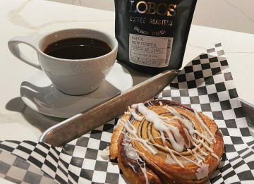 Bag of Lobos Roasted Cofffee, cup of coffee and pastry