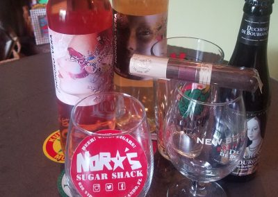 Nora's Sugar Shack with glasses, bottles of wine and a cigar.